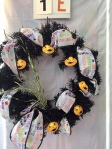 Halloween wreath with themed ribbon and smiling pumpkins